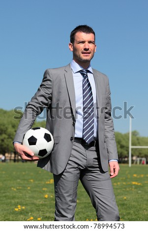 businessman with ball in a park in summer - stock photo