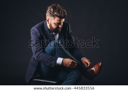 businessman with beard in studio, isolated black, suit