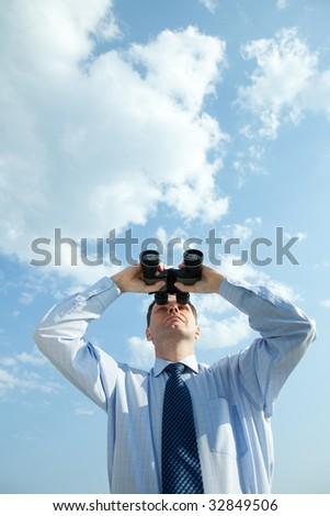 Businessman with binoculars against blue sky - stock photo