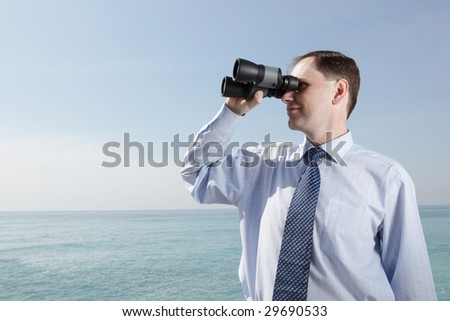 Businessman with binoculars against sea background - stock photo