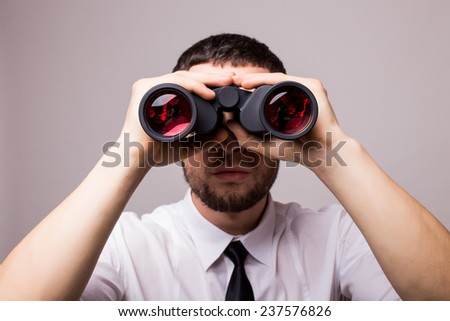 Businessman with binoculars. Over gray background - stock photo