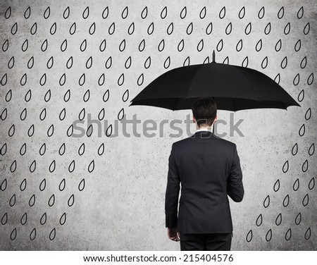 Businessman with black umbrella standing under drawing storm. Photo over concrete background - stock photo