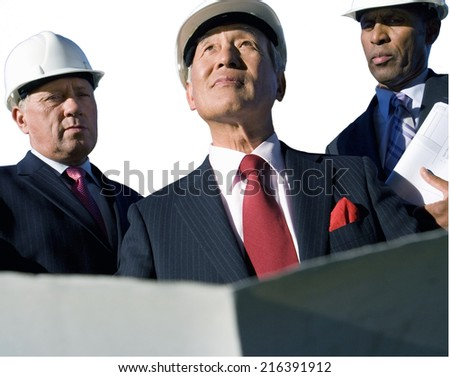 Businessman with blueprint by colleagues, in hardhats, low angle view, cut out - stock photo