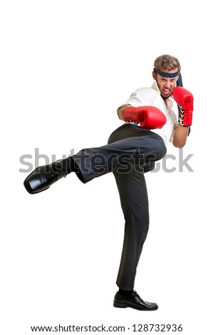 Businessman with boxing gloves kicking high - stock photo