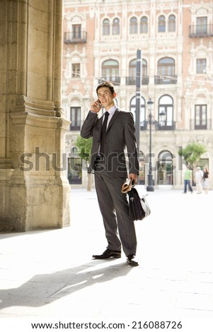 Businessman with briefcase and newspaper using mobile phone - stock photo