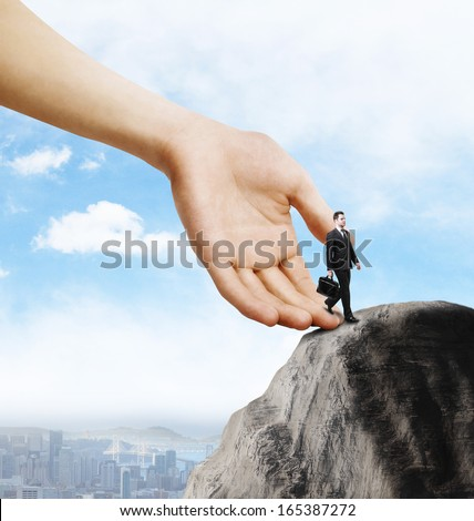 businessman with briefcase walking at big rock - stock photo