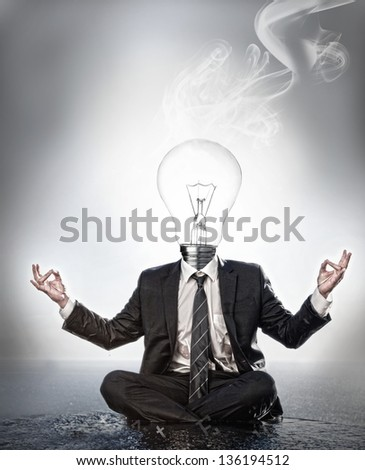 Businessman with bulb head sitting in meditation position with smoke rising on grey background - stock photo