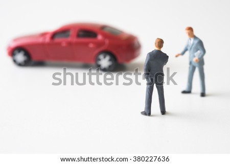 Businessman with car dealer thinking to buy a new red sport car. - stock photo
