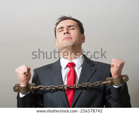 Businessman with chained hands - stock photo