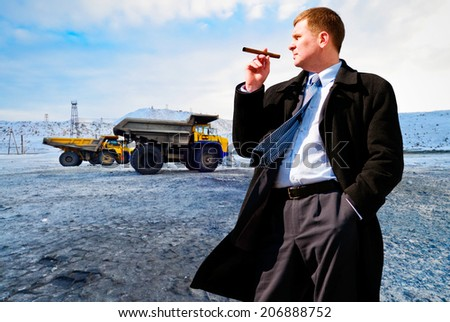 Businessman with cigar on industrial background - stock photo