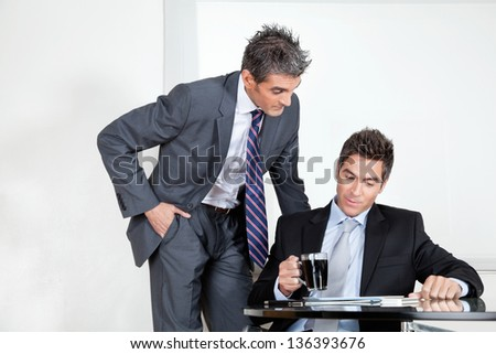 Businessman with coffee cup in a meeting with colleague at office - stock photo