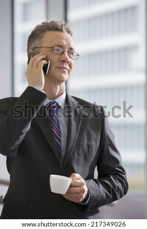 Businessman with coffee cup using cell phone in office - stock photo