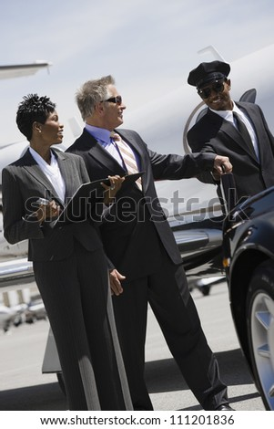 Businessman with colleague taking his briefcase from driver at airfield - stock photo