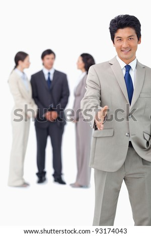 Businessman with colleagues behind him extending his hand against a white background