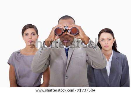 Businessman with colleagues using binoculars against a white background - stock photo