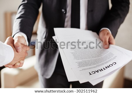 Businessman with contract handshaking with partner - stock photo