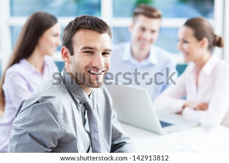 Businessman with coworkers in background - stock photo