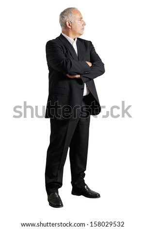 businessman with crossed hands looking at something - stock photo