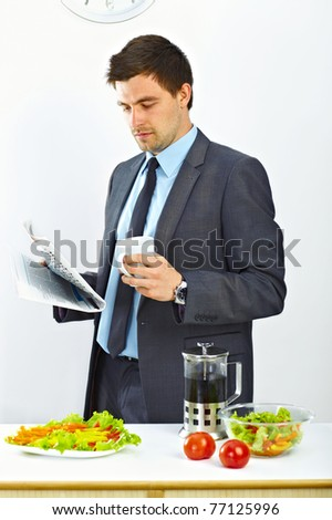 Businessman with cup of coffee reading newspaper in the kitchen - stock photo