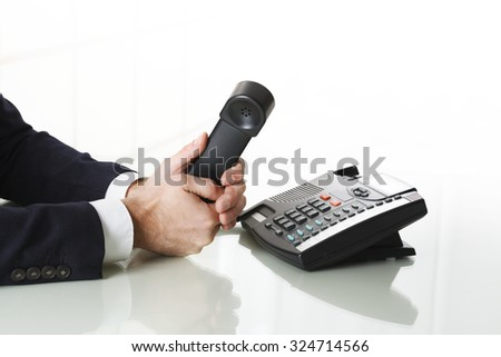 Businessman with dark gray suit dialing the number on a black landline telephone.  Closeup of his hand and the telephone on a white background. Concept of business and communication. - stock photo