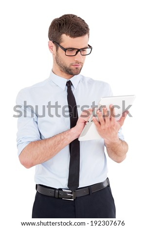 Businessman with digital tablet. Cheerful young man in formalwear and glasses working on digital tablet while standing isolated on white background - stock photo