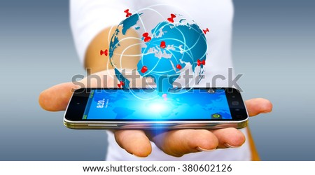 Businessman with digital world map and pins floating over his mobile phone - stock photo