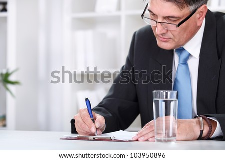 Businessman with document,  signing a contract with  pen - stock photo