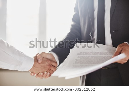 Businessman with documents congratulating his partner - stock photo