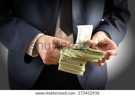Businessman with dollars in hands isolated on white