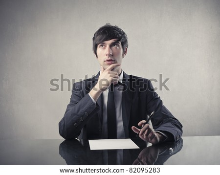 Businessman with doubtful expression doing a test - stock photo