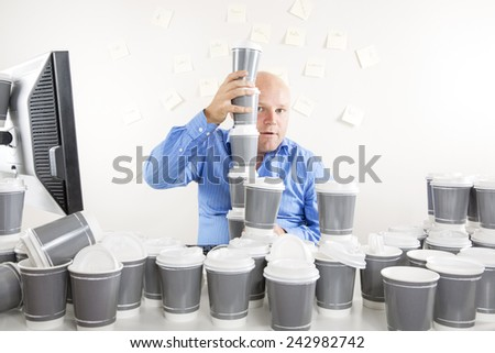 Businessman with extreme coffee addiction - stock photo