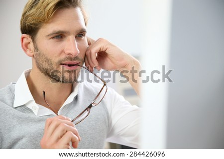 Businessman with eyeglasses sitting in front of desktop computer screen