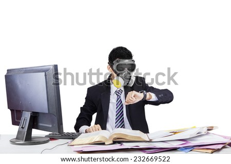 Businessman with gas mask working in workplace and looking at his timepiece - stock photo