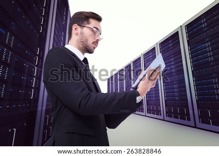 Businessman with glasses using his tablet against server hallway