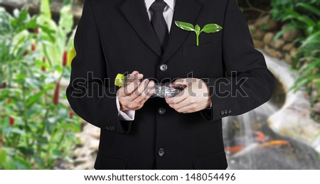 businessman with green seedling in the pocket destroy plastic bottle  for environment on plentifully garden background