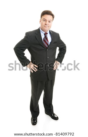 Businessman with hands on hips and a skeptical expression.  Full body isolated. - stock photo