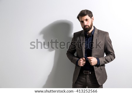Businessman with hands on his suit jacket standing against white wall. Mock up