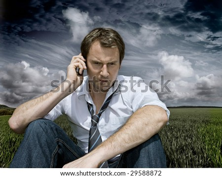 businessman with handy on a field with dark clouds behind