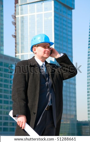 Businessman with hard hat talking on cell phone and holding drawing in his hand,on skyscrapers background - stock photo