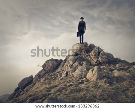businessman with hat and briefcase on the top of mountain - stock photo