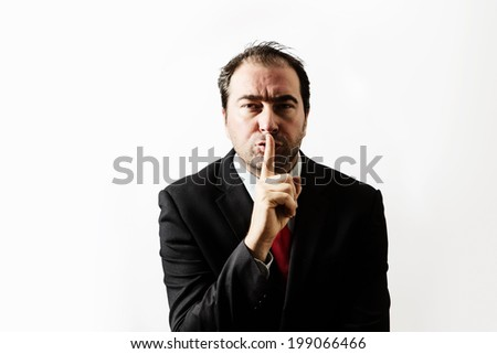 businessman with his finger up to his lips telling you to be quite - stock photo