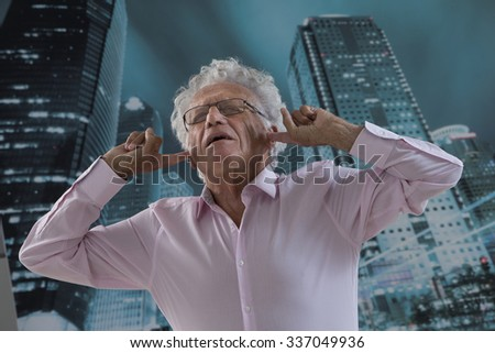 Businessman with his fingers in ears - stock photo