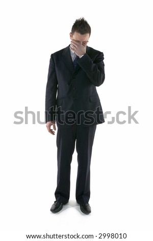 Businessman with his head in his hand having made a terrible mistake - stock photo