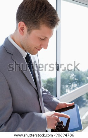 Businessman with his tablet in front of the window - stock photo