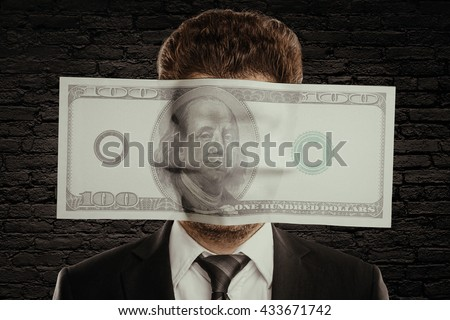 Businessman with huge hundred dollar bill against face on black brick wall background. Corruption concept - stock photo