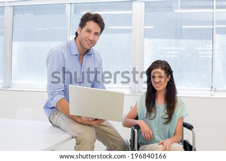 Businessman with laptop and businesswoman in wheelchair in the office - stock photo