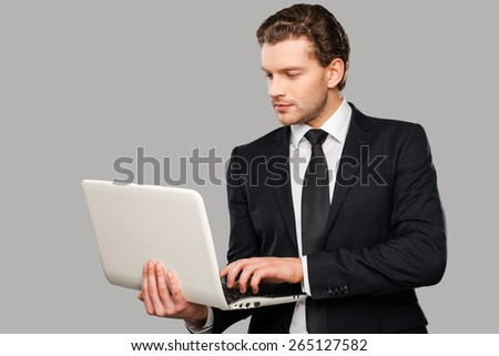 Businessman with laptop. Confident young man in formalwear working on laptop while standing against grey background - stock photo