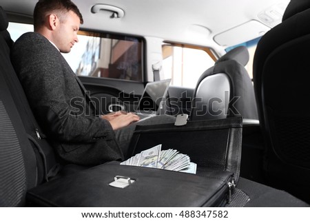 Businessman with laptop in a car. Case with money, close up