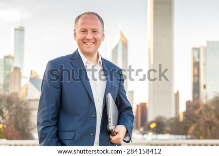 Businessman with laptop in front of office buildings - stock photo
