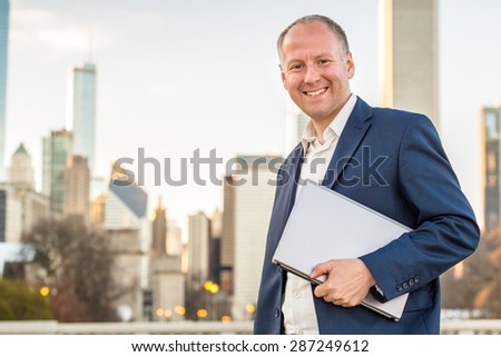 Businessman with laptop in front of skyscrapers - stock photo